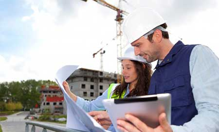 Engineer and construction worker studying blue print document